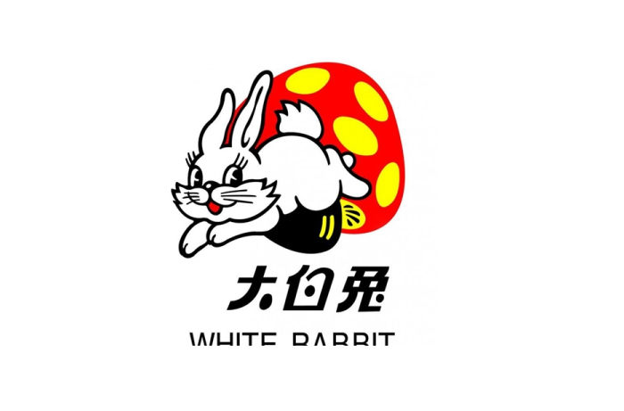 """大白兔奶糖的前身源自1943年上海""""爱皮西糖果厂""""。该公司的商人尝试过当时英国的牛奶糖之后,认为味道不错,经过半年后便仿制出自家品牌的国产奶糖。包装则使用红色米奇老鼠的图案,并名为""""ABC米老鼠糖""""。由于售价比舶来品便宜,所以广受民众喜爱。直至1950年代,该糖果公司被收归国有,米奇老鼠被视为崇洋媚外的符号,于是包装图案改成白兔,并于1959年作为中华人民共和国国庆十周年的献礼产品。"""